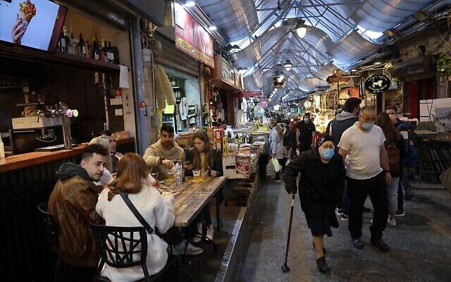 تصویر: مردم حین صرف غذا در رستورانی در بازار بزرگ اورشلیم، پس از بازگشایی رستورانها، بارها، و کافه ها بروی دارندگان «پاسپورت سبز» در ۱۱ مارس ۲۰۲۱. (Emmanuel DUNAND / AFP)