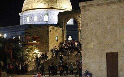تصویر: معترضان فلسطینی حین تماشای زدوخورد با نیروهای امنیتی اسرائيلی در تپهٔ معبد مقدس در اورشلیم، ۱۷ مه ۲۰۲۱. (Photo by Ahmad GHARABLI / AFP)