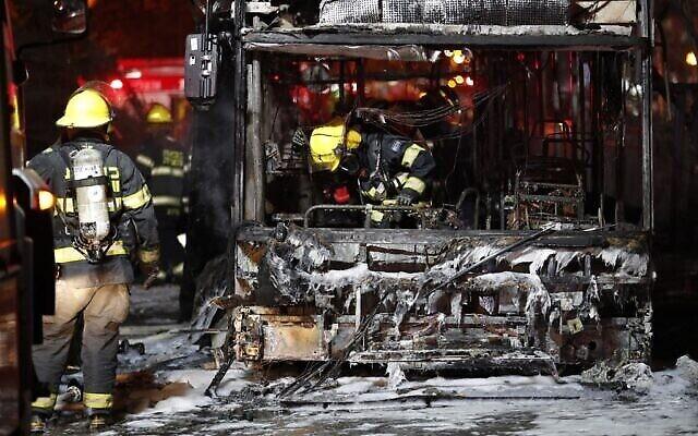مأموران آتش نشانی اتوبوسی در شهر «هولون» نزدیک تل آویو که مورد  اصابت راکت های مهاجم غزه قرار گرفت را وارسی می کنند؛ ۱۱ مه ۲۰۲۱. (Ahmad GHARABLI / AFP)