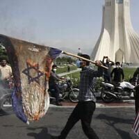 ایرانی ها در رژهٔ روز قدس در میدان آزادی تهران، پایتخت ایران، پرچم های اسرائیل را به آتش می کشند، پرچم ایالات متحده را لگدمال می کنند، ۷ مه ۲۰۲۱. (AFP)
