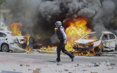 تصویر: یک آتش نشان اسرائیلی در شهر اشکلون، جنوب اسرائيل، از کنار اتوموبیلهایی که مورد اصابت راکتهای نوار غزه قرار گرفتند، می گذرد؛ ۱۱ مه ۲۰۲۱. (AP Photo/Ariel Schalit)
