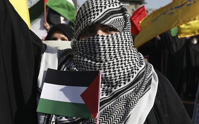 تصویر تزئینی: زنی در تظاهرات هواداران فلسطینیان در تهران که صورت خود را به شیوهٔ شبه نظامیهای فلسطینی و لبنانی پوشانده و پرچم فلسطینی در دست دارد؛ ایران، تهران، ۱۹ مه ۲۰۲۱.  (AP Photo/Vahid Salemi)