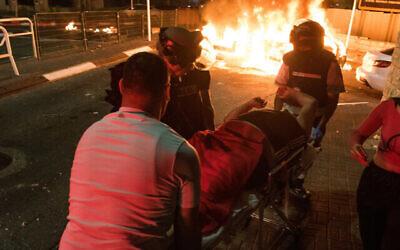 کادر درمانی در حال انتقال مردی که در زدوخوردهای میان عرب ها و یهودیان در «اکره»، شمال اسرائیل، مجروح شد؛ ۱۲ مه ۲۰۲۱. (Roni Ofer/Flash90)