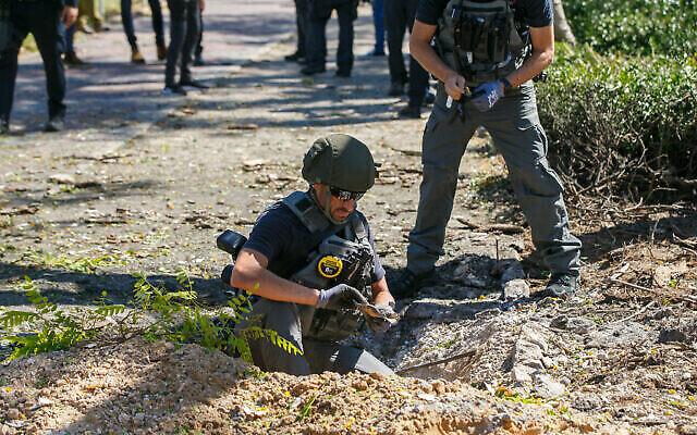 نیروهای امنیتی اسرائیل در شهر جنوبی اشدود در اسرائیل، در محلی که قطعه ای از راکتی که از نوار غزه شلیک شده افتاده است، ۱۹ مه ۲۰۲۱. (Flash90)