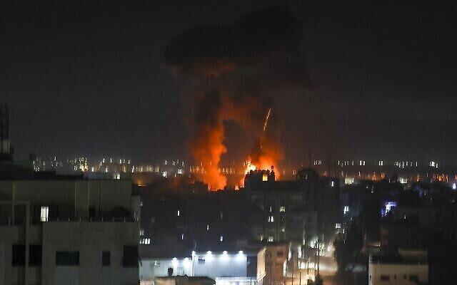 هواپیماهای نیروهای دفاعی اسرائيل ناحیهٔ محصور فلسطینیان را بمباران کردند و انفجار آسمان شب را بر فراز برج های شهر غزه نورانی کرده؛ ۱۶ ژوئن ۲۰۲۱. (MAHMUD HAMS / AFP)