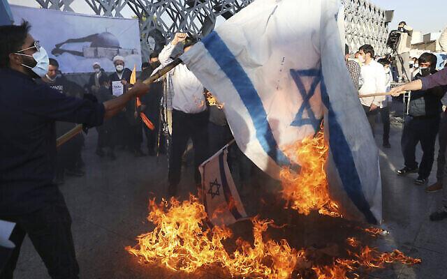 تصویر: در تظاهرات هواداران فلسطینیان در تهران، حاضران نمادهای پرچم اسرائیل را می سوزانند؛ تهران، ایران، ۱۹ مه ۲۰۲۱. (Vahid Salemi/AP)