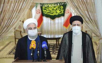تصویر: در عکسی از وبسایت رسمی ریاست جمهوری ایران، حسن روحانی رئیس جمهور، چپ، حین گفتگو با رسانه ها پس از ملاقات با ابراهیم رئیسی، رئیس جمهور منتخب، راست، که در حال حاضر رئیس قوهٔ قضائیه است؛ تهران،  ایران، ۱۹ ژوئن ۲۰۲۱. (Iranian Presidency Office via AP)