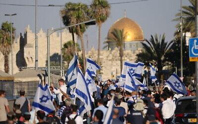 مردان یهودی در رژهٔ پرچم در نزدیکی شهر قدیم اورشلیم با پرچم اسرائیل پایکوبی می کنند، ۱۵ ژوئن ۲۰۲۱.  (Yonatan Sindel/Flash90)
