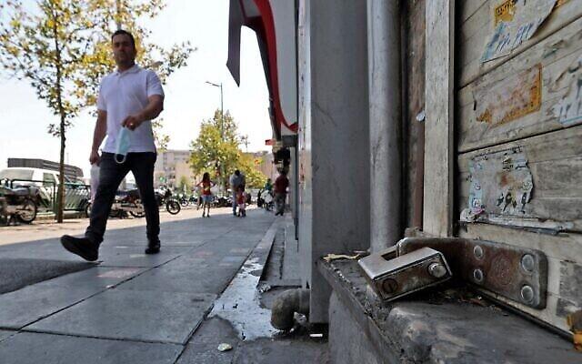 تصویر: مرد ایرانی در تهران، پایتخت ایران، از مقابل مغازه ای با کرکرهٔ کشیده می گذرد؛ ۲۰ ژوئیهٔ ۲۰۲۱.  (ATTA KENARE / AFP)