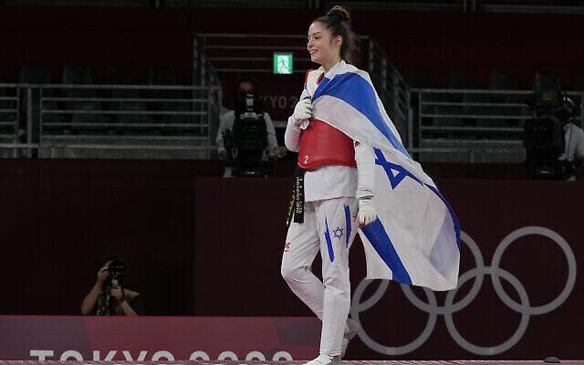 آویشاگ سمبرگ از اسرائيل پس از شکست «رقیه یلدریم» از ترکیه و کسب مدال برنز در تکواندوی ۴۹ کیلوگرم زنان در بازیهای تابستان المپیک ۲۰۲۰ توکیو، می رود که از رینگ خارج شود؛ شنبه ۲۴ ژوسیه ۲۰۲۱، توکیو، ژاپن.  (AP Photo/Themba Hadebe).