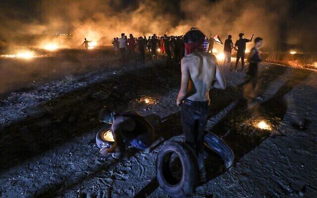 تصویر: معترضان فلسطینی در حال آتش زدن لاستیک ماشین در تظاهراتی در مرز میان نوار غزه و اسرائیل در شرق شهر غزه، ۲۸ اوت ۲۰۲۱. (Photo by MAHMUD HAMS / AFP)