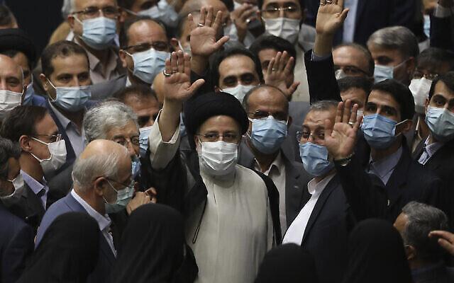 تصویر: ابراهیم رئیسی، رئیس جمهور ایران، وسط، در حلقهٔ گروهی از قانونگزاران پس از آنکه در پارلمان تهران به عنوان رئیس جمهوری سوگند یاد  کرد، به سوی خبرنگاران دست تکان می دهد؛ ایران، پنجشنبه، ۵ اوت ۲۰۲۱.  (AP Photo/Vahid Salemi)