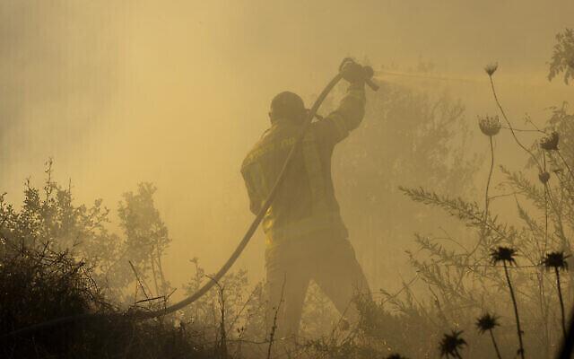 مأموران آتش نشانی در تلاش به اطفای حریق نزدیک موشاو گیوات یئریم، نزدیک اورشلیم، ۱۶ اوت ۲۰۲۱.  (Olivier Fitoussi/Flash90)