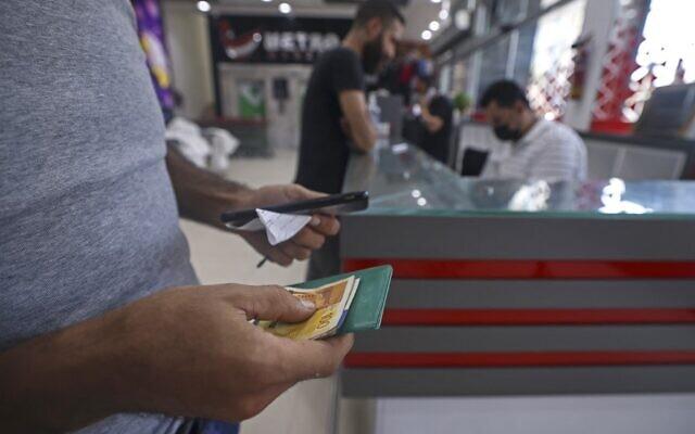 تصویر: یک فلسطینی حین دریافت کمک مالی در سوپرمارکتی در شهر غزه، ۱۵ سپتامبر ۲۰۲۱ که تحت برنامهٔ کمکهای مالی بشردوستانه از سوی دولت قطر پرداخت می شود. (Mahmud Hams/AFP)