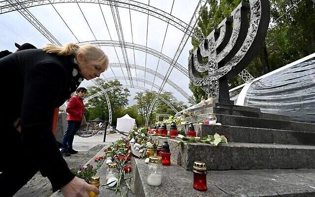 تصویر: مردم در روز ۲۹ سپتامبر ۲۰۲۱، هشتادمین سالگرد کشتار «بابی یار»، از بزرگترین کشتارهای یهودیان در جنگ جهانی دوم، پای بنای یادبود «منورا» در کی-یف شمع روشن می کنند. (Sergei SUPINSKY / AFP)