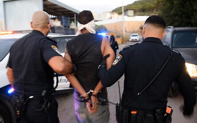 پلیس ذکریا را که از بهمراه تنی چند زندانی امنیتی دیگر از زندان اسرائیل گریخته بود در شمال اسرائیل دستگیر کرده و به ماشین گشت پلیس منتقل می کند، ۱۱ سپتامبر  ۲۰۲۱. (Israel Police)