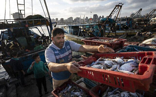 تصویر: ماهیگیری در حال بار کردن گاری برای حمل بار به بازار شهر غزه، هنگامیکه شمار محدودی قایق در پی جنگ ۱۱ روزه میان حماس و اسرائيل،  اجازهٔ بازگشت به دریا یافتند؛ ۲۳ مه ۲۰۲۱.  (AP Photo/John Minchillo)