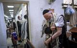 تصویر: «یهوشوآ داتسینگر»، بازماندهٔ هولوکاست، حین بستن تفیلین به بازوی خود، اندکی بالاتر از خالکوبی شمارهٔ شناسایی اردوگاه کار اجباری آشویتس، هنگام عبادت صبحگاهی در کنیسا، بنی براک، اسرائیل، ۲۱ سپتامبر ۲۰۲۰.  (Oded Balilty/AP)