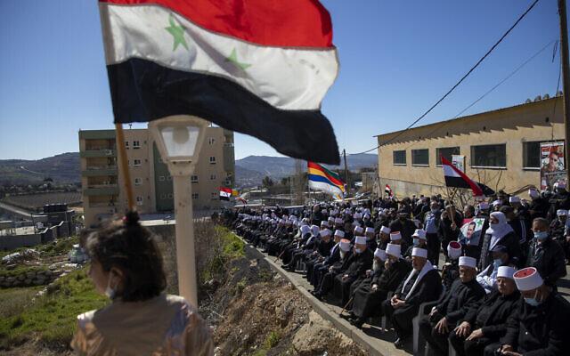 تصویر: در عکسی از ۱۴ فوریهٔ ۲۰۲۱، حامیان دروزی بشار اسد رئیس جمهوری سوریه مشاهده می شوند که با پرچم هایی در دست، در راهپیمایی نزدیک به مرز سوریه در میدال شمس، بازگشت بلندیهای جولان به سوریه را مطالبه کردند. بلندیهای جولان در ۱۹۶۷ به تصرف اسرائیل درآمد. (AP Photo/Oded Balilty, File)