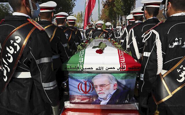 تصویر: در عکسی از مراسم تشییع «محسن فخری زاده» دانشمند هسته ای ایرانی که ترور شد، یک ارتشی کنار تابوت در پرچم پیچیدهٔ او در تهران ایستاده است؛ ایران، ۳۰ نوامبر ۲۰۲۰. (Iranian Defense Ministry via AP)