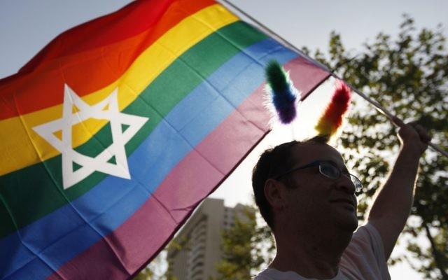 Un homme agite un drapeau arc-en-ciel à la Gay Pride de Jérusalem (Crédit : Miriam Alster / FLASH90)