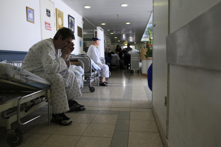 An Israeli patient waits in the corridor of the Barzlai Medical Center. Nurses from Barzilai Hospital in Ashkelon and Soroka hospital in Beersheva left their stations for two hours to protest an excessive work burden. February 15, 2012. (photo credit:Tsafrir Abayov/Flash90