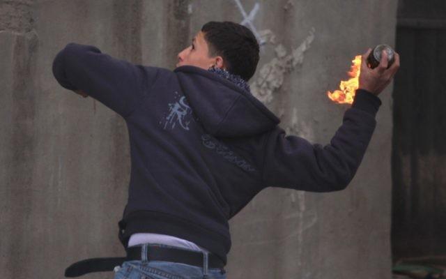 Un Palestinien jette une bombe incendiaire sur des soldats au checkpoint de Qalandiya, près de Ramallah. Photo d'illustration. (Crédit : Issam Rimawi/Flash90)