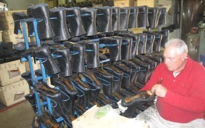 Un travailleur à l'usine Brill travaille sur une chaussure de l'armée  (Crédit : Mitch Ginsburg/Times of Israel)