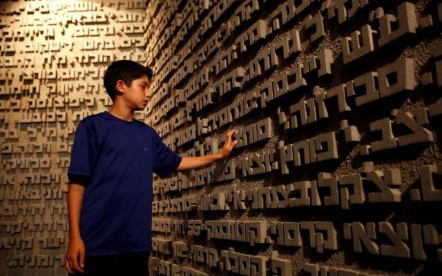 """""""Chaque personne a un nom"""". Un garçon touche les noms des victimes de l'Holocauste (Crédit : Flash90)"""