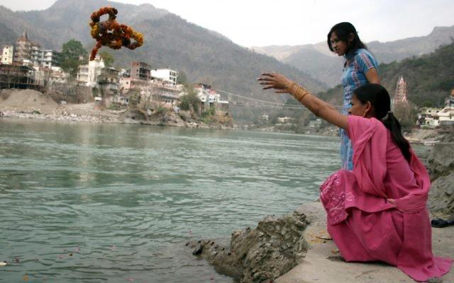 Une femme jette une couronne de fleur dans le Gange (photo credit: Liron Almog/Flash90)