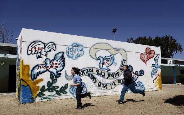 Des élèves courent devant un abri anti-bombes dans une école élémentaire d'Ashkelon. Illustration. (Crédit : Tsafrir Abayov/Flash90)
