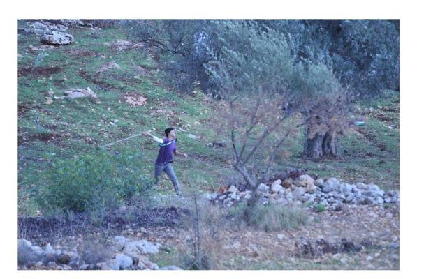 Un jeune Palestinien près de la barrière de sécurité à Bilin (Crédit : autorisation IDF)