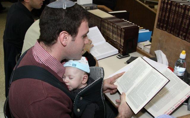 Un père et son bébé alors qu'il étudie la Torah. (Gershon Elinson/Flash90)