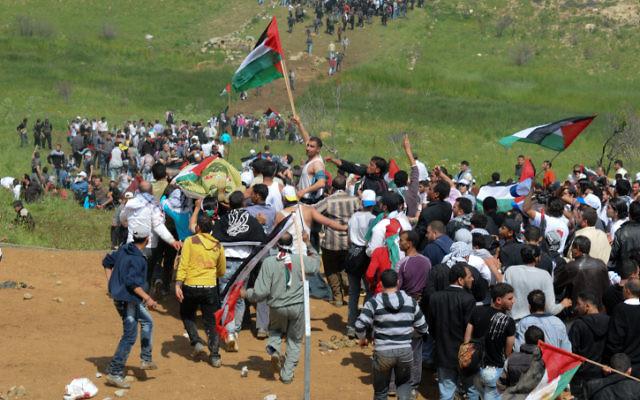 Des manifestants arabes avec des drapeaux palestiniens à la frontière syrienne le jour de la Nakba 2011 (Crédit :  Hamad Almakt/ Flash90)