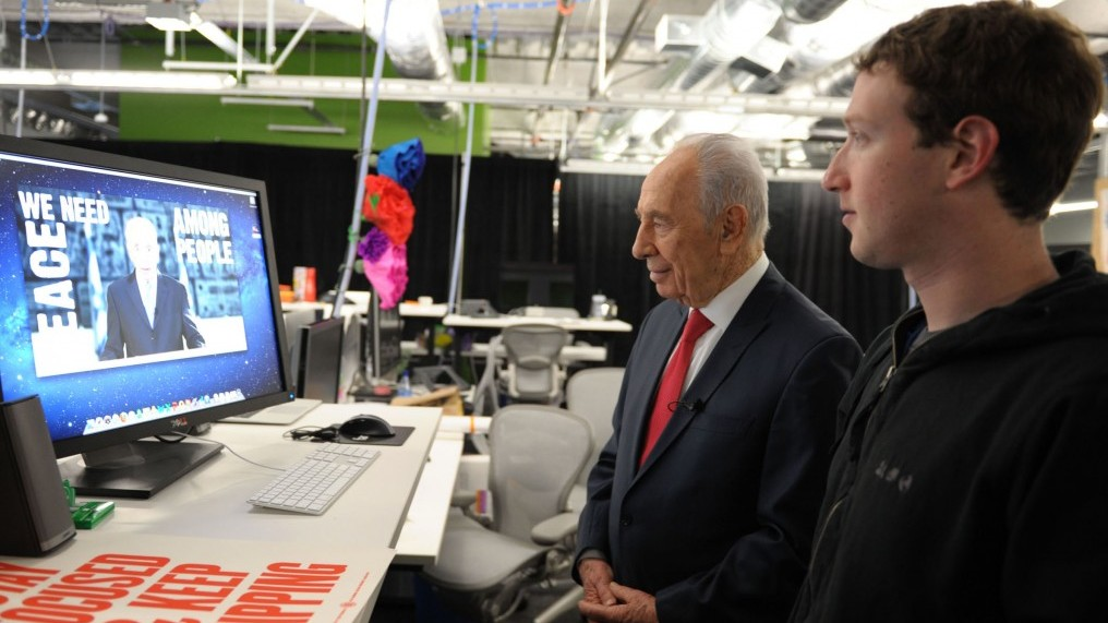 President Shimon Peres works on his Facebook page with Mark Zuckerberg, founder of Facebook, looking on (photo credit: Moshe Milner/GPO/Flash90)