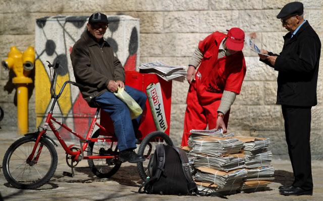 Un distributeur du journal Israel Hayom offre des copies gratuites aux passants à Jérusalem (Crédit :  flash90)