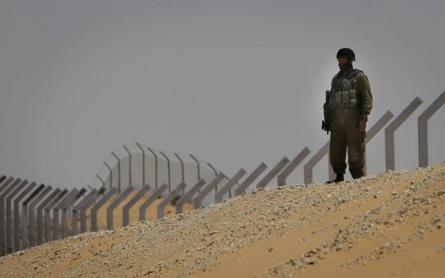Un soldat israélien debout le long d'une section de la clôture nouvellement construite le long de la frontière avec le Sinaï en arrière-plan. (Crédit : Tsafrir Abayov/Flash 90)