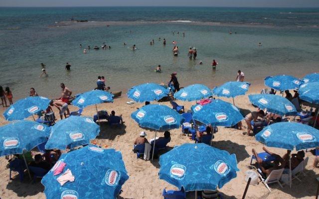 Beach goers at the seashore in Bat Yam (photo credit: Alana Perino/Flash90)