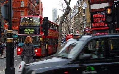 Une femme à un feu rouge, dans l'une des rues les plus fréquentées de Londres. Illustration. (Crédit : Gili Yaari/Flash90)