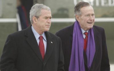 Le président George W. Bush marche aux côtés de son père, George H.W. Bush, à droite, sur la base de l'armée de l'air  Andrews, dans le Maryland, en décembre 2008 (Crédit : AP/Evan Vucci)