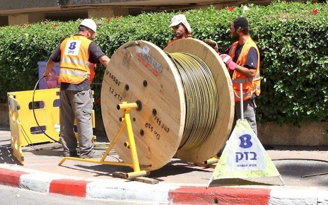 Des ouvriers de Bezeq installant des câbles de fibre optique. (Crédit : Autorisation)