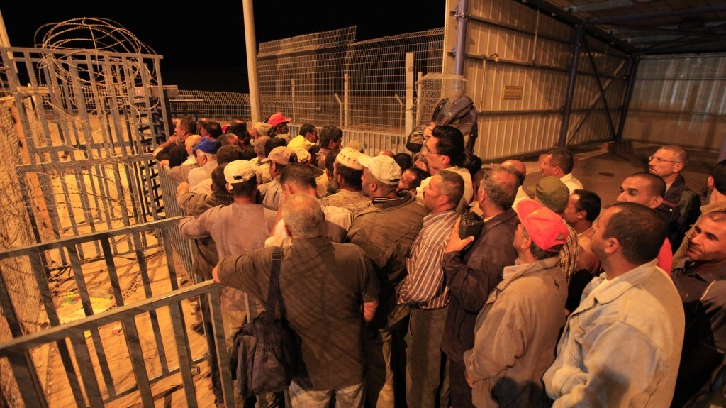 Palestinians line up before dawn to cross a checkpoint near Beersheba to attend work in Israel (photo credit: Tsafrir Abayov/Flash90/File)