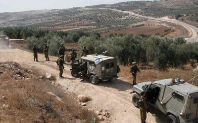 Des soldats israéliens protègent des Palestiniens lors d'une récolte d'olives à Hébron (Crédit : Najeh Hashlamoun/Flash90)