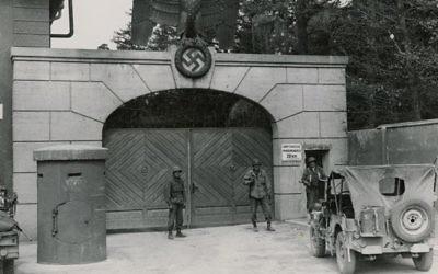 Les troupes américaines postées à l'entrée du camp de concentration de Dachau (Crédit : US National Archives/Wikimedia Commons)