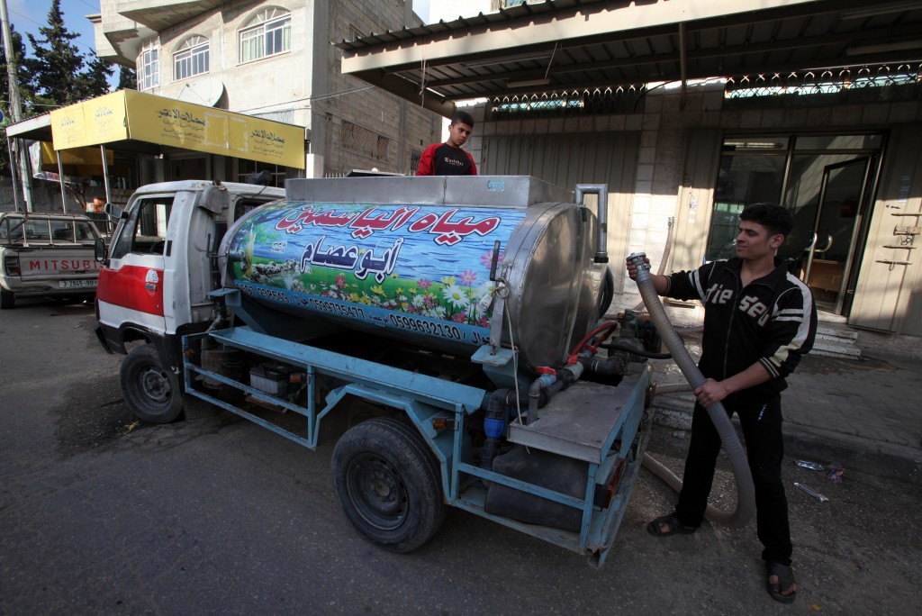 A Palestinian man fills a tank with clean water, to be trucked for families who don't have safe drinking water at their homes in Gaza City, on March 22, 2012 (photo credit: Wissam Nassar/Flash90)