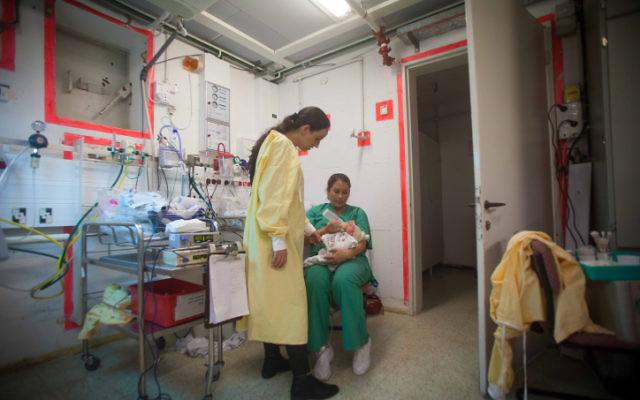 Une infirmière s'occupe d'un nourrisson dans un abri de l'hôpital Barzilai alors qu'une sirène retentit, avertissant de l'arrivée possible de roquettes à Ashkelon, le 15 novembre 2012. (Crédit : Uri Lenz/Flash90)