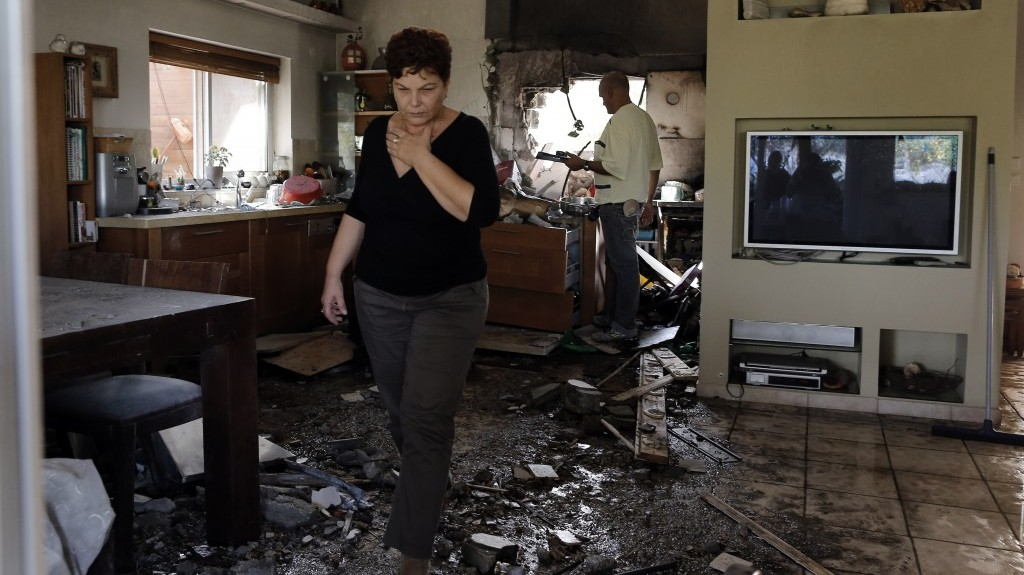 An Israeli woman walks through a house in southern Israel that was hit by a rocket fired from the Gaza Strip during Operation Pillar of Defense (photo credit: Tsafrir Abayov/Flash90)