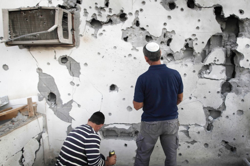 Israeli men inspect damage to a house in Ofakim damaged by rocket fire from Gaza. (photo credit: Flash90)