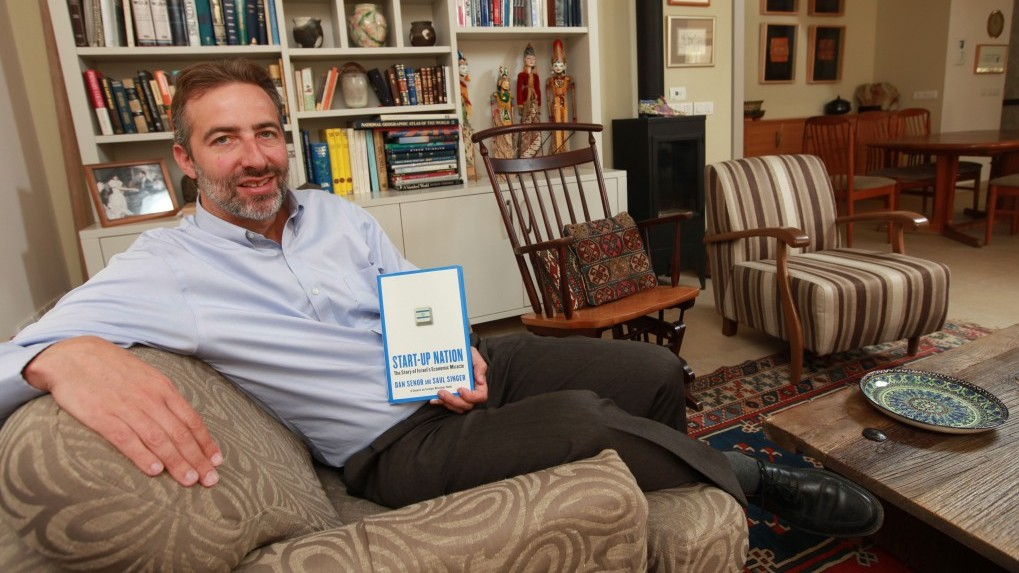 "Saul Singer with a copy of ""Start-Up Nation"" (Photo credit: Nati Shohat/Flash90)"