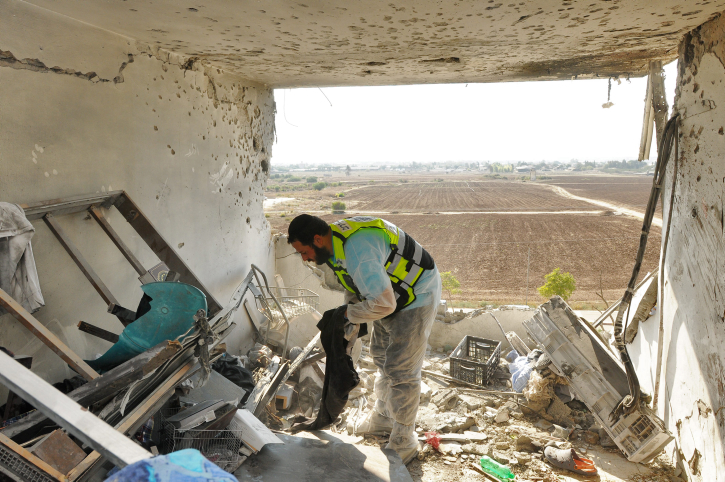 A ZAKA volunteer looks for human remains in the Kiryat Malachi apartment where three Israelis were killed by a rocket fired from Gaza Thursday, November 15 (photo credit: Yossi Zeliger/Flash90)